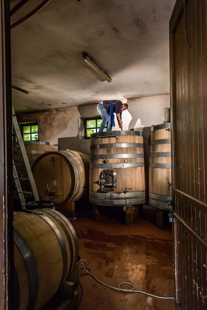 Fotografia di una persona in cima a una grande botte di legno
